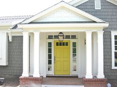 The columns, the yellow door against the crisp white and stormy grey, the texture of the siding.