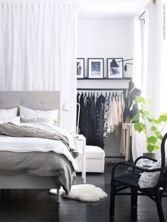 In lieu of placing the bed against the wall, set it a couple of feet away, utilizing the extra space as a faux closet, separated by a thin curtain.