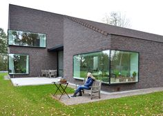 Large windows protrude away from the brown brickwork of this house in Belgium
