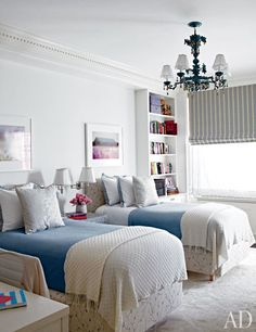 In a children's room, sconces from Remains Lighting are mounted between Charles H. Beckley beds upholstered in a Fabricut linen | archdigest.com