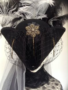Black Tricorn pirate hat with black and gray rear tulle veil with matching crown feathers, centre piece of Gothic cross and keys, sides are pinned back
