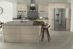 Jura collection Attractive gloss-cream fitted kitchen with wide-format units, spacious island breakfast bar, American-style fridge and contemporary appliances