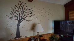 "Beautiful #uppercaseliving blustery #tree on #texturedwall. The great thing about this piece is that you can place the leaves wherever you want. I love that a small pile was placed at the base of the tree to ""ground"" the image.  #ultorreh #nature #wainscoting #vinyl #autumn"