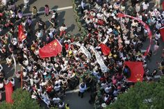 CHINA-JAPAN/rotesters hold up Chinese national flags and banners as they walk past paramilitary policemen during a protest on the 81st anniversary of Japan's invasion of China, outside a Japanese consulate in Shanghai, September 18, 2012. Japanese businesses shut hundreds of stores and plants and the country's embassy suspended services in China on Tuesday as anti-Japan protests reignited and risked dragging a territorial dispute between Asia's two biggest economies deeper into crisis…