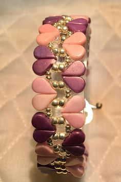 Sweetheart is a band style bracelet with heart shaped units made from pink and purple Amos par Puca glass beads. Silver seed beads and a silver-toned heart-shaped toggle clasp add design to the bracelet. The bracelet measures 7.25 inches in length and .75 inches in width. An