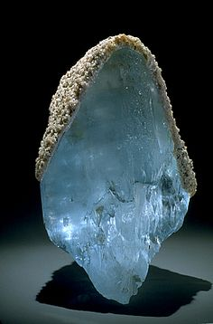 Topaz with lepidolite ~~ Most topaz come from pegmatites. This large crystal capped with lepidolite is naturally blue which is rare in nature. Most blue topaz is man-made by irradiating and heating colorless or yellow-brown topaz.