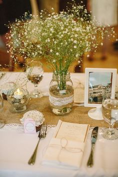 White tablecloth, burlap runner, mason jar decor. Wildflowers and floating candles. Reception tables, done!