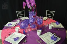 Purple Passion - Purple has always been a color of royalty, which is impeccable for this extraordinary day. Shades of purple vanda orchids floating in crystal vases sets the table with enchantment and distinction. | #PennockFloral