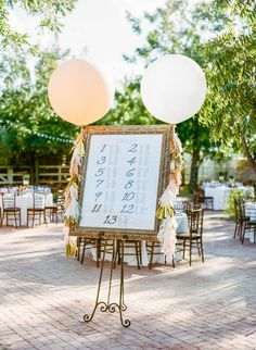 When it comes time to escort your guests to their seats at the reception, it becomes a difficult task. You have a herd of (hungry and thirsty) people trying to find their names on either cards, tags, or better yet charts. To eliminate some stress, display your seating arrangements during cocktail hour so that they can take their time to look. Here are a few creative ideas that come to our minds: 1. Framed Chart - Accessorize with tassel balloons to create a focal point...