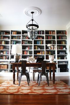 The striking, high-contrast light fixture above the desk really adds drama to this space, and helps make those built ins look even taller  Eclectic Home Office by Emily A. Clark