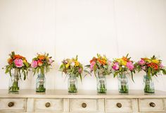 Hanging chair vases lined up on bride and groom table with bride's bouquet in the center.