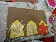Three little Pigs Project -- The children cut out three house shapes, then glued straw to one, sticks to a second and red squares of paper to the third. After they finished, they used a pig stamper to add a pig on top of each house.