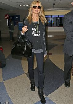 Edgy chic: Heidi Klum landed in LAX on Sunday in a black blazer with leather sleeves over a black and grey sweater