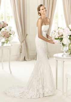 The boldest brides will see all their wishes come true with the dazzling Balira model from the Pronovias 2013 collection. This original bridal dress skims the bride's figure, delicately embracing her curves. This eye-catching tulle, imperial waist gown has a strapless neckline with white and silver precious stones centrally placed just below the bust.  The mermaid skirt with guipure lace details make this an elegant and flattering choice.