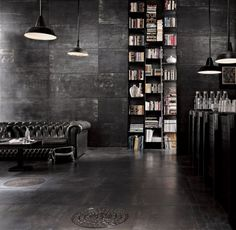 A dark interior with couch and bookshelf