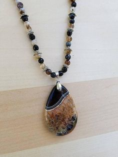 This stunning beaded gemstone necklace is one of a kind. This is a unique statement piece that features micro faceted agate gemstone beads with lovely silver metal spacers and a breathtaking orange druzy geode agate gemstone pendant. The necklace measures about 22 long, and I am