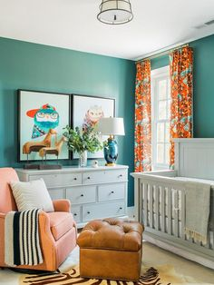 Blue and orange nursery features walls painted blue, Sherwin Williams Riverway, lined with a light gray crib, Bassett Chesapeake Full Panel Crib, dressed in white and gray crib bedding flanked by windows dressed in orange and turquoise blue curtains, DwellStudio Vintage Plumes Fabric.