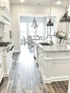 I'm obsessed with this white kitchen! The pendant lights and wood tile floor makes for a really gorgeous room! #ad