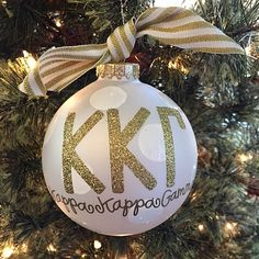 Kappa Kappa Gamma - Glitter Gold Ornament: The Kappa Kappa Gamma Gold Glitter Ornament is a must-have for any stylish sorority woman. With its classic white stripe ribbon and sparkly gold greek lettering, this ornament is the perfect holiday gift.  Comes packaged in a coordinating gift box for perfect present presentation.
