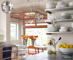 The most interesting features in the remodeled home are the three glass-panel garage-style doors -- each painted orange -- that can easily roll up to help cool the home in the summer. This door in the kitchen opens up to the deck, inviting easy indoor-outdoor living./