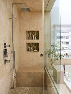 Walk-In Shower: Travertine tile from floor to ceiling keeps color and pattern to a minimum for a tranquil shower under the modern rain showerhead. The backs of built-in niches are tiled with the same glass mosaic as the vanity wall for a unified look and visual interest.
