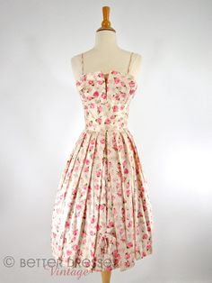 Wow! This 1950s silk party dress has all the touches that make mid-century vintage so dreamy. The fabric is a mid-weight silk featuring beautiful pink and fuchsia roses with green leaves on cream. Spa