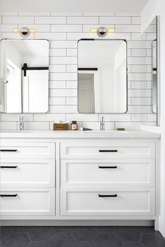 Fresh all-white bathroom with subway tiled walls, recessed panel Shaker cabinets and slate tile flooring.