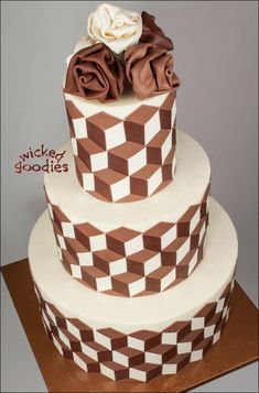 Round three tier wedding cake frosted with smooth buttercream frosting and three natural tones ofmodeling chocolate that gives the optical illusion impression of 3D cubes. Fabric flowers on top of the cake are also made from rolled modeling chocolate