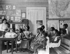 African American children and teacher in classroom studying