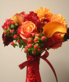 Berries, roses, and cala lilies wrapped with a sweet satin bow for a Fall bridal bouquet