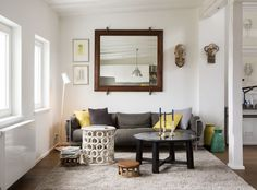 Modern living room accesorized with a big mirror and grey sofa. Combination of yellow and grey pillows give an additional touch. #interior #design #modern #livingroom #bigmirror #yellow #homedecor