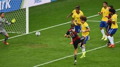 Thomas Mueller of Germany scores his team's first goal past David Luiz and goalkeeper Julio Cesar of Brazil during the 2014 FIFA World Cup Brazil Semi Final match