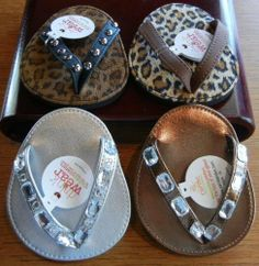 """Bling Flip Flop Attachable Coaster Set - 4 Styles by Carrie & Company. $24.75. Each coaster is approximately 4 1/2"""" long x 3 1/2"""" wide and are made of moisture resistant foam and fabric.. Set of four Bling Flip Flop Coasters in 4 assorted colors/styles.. Allow your guests to distinguish their glass in style with these unique and fun attachable coasters for the foot of their glass!. Slip a coaster onto the foot of the glass. It will travel with you, at the pool side, in the sa..."""