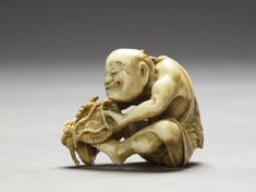 Netsuke in the form of a man making a matside. //  ivory, with carved decoration, and stained with pigment -  Date:     1780 - 1820 //   Artist/maker:      Kawakita Masanori (active 19th century) (carver)