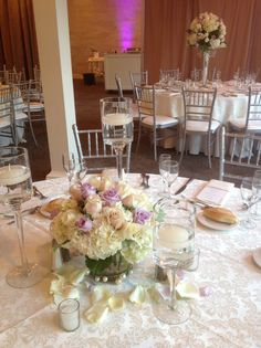 Wedding centerpiece of white hydrangea, Sahara roses, and lavender roses in pearl banded cylinder vase surrounded by pedestals with floating candles, rose petals and votives