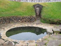 A bath built by Snorri Sturluson at his farm at Reykholt, around the year 1210. It's fed by water piped from separate hot and cold water springs, so the temperature can be adjusted to suit. The door in the hillside behind the bath leads to a tunnel which probably led back to Snorri's farmhouse.