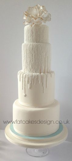 A tall four tier ivory wedding cake with vertical strings of pearls. Gold edged flower on top tier.
