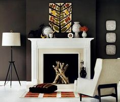 Chocolate brown paint wall color Eclectic living room. Tripod floor lamp, white stone fireplace, glass tile fireplace, modern wing back chair, orange white graphic rug, black red graphic throw pillow, Jonathan Adler vases and marble floors. Brown orange white living room colors.