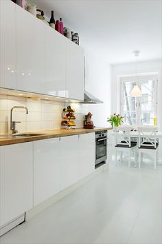 An apartment in Stockholm - white high gloss kitchen with wood/ oak top and pale floor. New kitchen inspiration Kitchen Decor, Kitchen Inspirations, Kitchen Style, Kitchen Flooring, White Gloss Kitchen, Clean Kitchen Cabinets, Home Kitchens, Kitchen Living, Gloss Kitchen Cabinets
