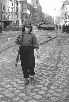 """by Erich Lessing. A burnt-out heavy tank """"Josef Stalin"""" IS 3 with a 122 mm gun near the Kilian barracks in Budapest. An insurgent walking home. After the defeat of the Revolution, she was sentenced to death and executed. Insurgent, Budapest Hungary, Soviet Union, Women In History, Vietnam War, Cold War, Historical Photos, World War Ii, Wwii"""