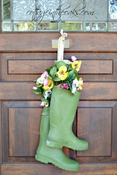 Forget what Nancy Sinatra says, these boots were made for...hanging on the door. It's not exactly a door wreath, but pretty close. Blogger Daune of Cottage in the oaks pops some bright blooms inside a favorite pair of galoshes for a fresh breath of spring. || @cottageintheoak