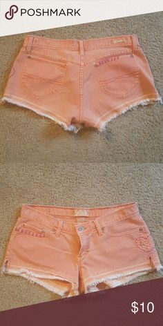 """Lucky Brand shorty shorts size 4/27 Very cute peachy color shorts with magenta peace sign heart stitching. Waist measures 15.25"""" dip 7"""" inseam 3"""". In great condition. Lucky Brand Shorts Jean Shorts"""