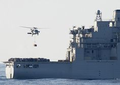 """An MH-60S assigned to the """"Wild Cards"""" of Helicopter Sea Combat (HSC) Squadron 23 departs dry cargo and ammunition ship USNS Wally Shirra (T-AKE 8) en route to amphibious assault ship USS Boxer (LHD 4) during a vertical replenishment."""
