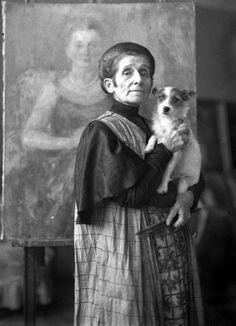 """Olga Boznańska w pracowni krakowskiej z pieskiem Kwi-Kwi na rekach, 1930/1931, fot. nieznany (Archiwum Fot. """"Ilustrowanego Kuriera Codziennego""""), Narodowe Archiwum Cyfrowe // Olga Boznańska in her Krakow studio with her dog Kwi-Kwi, 1930-1931, unknown photographer"""