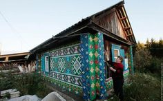 A pensioner works on a mosaic, made from plastic bottle caps which decorate the facade of her house, in the village of Kamarchaga