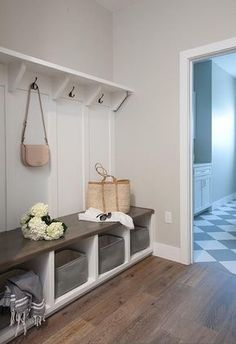 Oak wood floors accent gray walls highlighting a white built in bench fitted with cubbies holding small gray storage baskets.