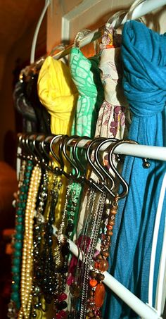 "An over the door towel rack to organize scarves with shower curtains rings & necklaces on ""S"" hooks."