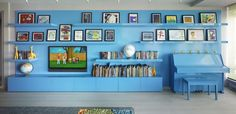 Mom Kelly's California childhood inspired the color pops, including a wall of blue, which displays kids' artwork, books, and more.  Source: Annie Schlechter for Incorporated