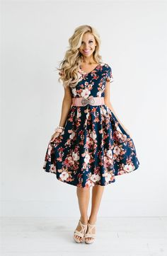 This adorable fit and flair dress features large pleats in the skirt, short sleeves, a small v neckline and princess seams. It features a dreamy dusty pink and cream floral print on a textured navy base.