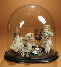 Miniature antique dolls in glass dome.